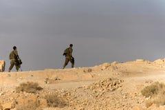 Vue de côté de deux hommes d'infanterie avec des armes dans la marche dans le désert dans un jour ensoleillé chaud contre le ciel photos libres de droits
