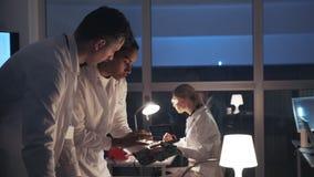 Vue de côté de deux ingénieurs de développement de l'électronique parlant du conseil électronique et expliquant des détails de le banque de vidéos
