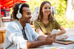 Vue de côté de deux jeunes amis de sourire s'asseyant par la table Image libre de droits