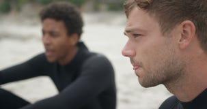 Vue de côté de deux surfers masculins détendant sur la plage 4k banque de vidéos