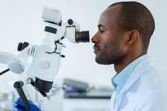 Vue de côté du dentiste masculin à l'aide du microscope Image libre de droits