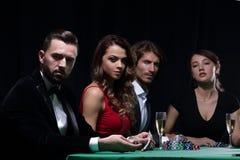 Vue de côté du groupe de personnes jouant le tisonnier ensemble dans le casino Photographie stock