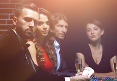 Vue de côté du groupe de personnes jouant le tisonnier ensemble dans le casino Images libres de droits