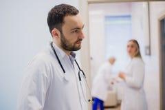 Vue de côté du jeune docteur réfléchi dans l'uniforme médical écoutant le patient photographie stock