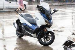 Vue de côté du stationnement 2018 blanc-bleu de moto de Honda Forza 300 sur la promenade latérale en pleuvant le jour images stock