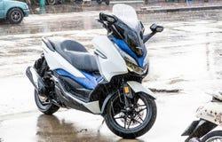 Vue de côté du stationnement 2018 blanc-bleu de moto de Honda Forza 300 sur la promenade latérale en pleuvant le jour photographie stock