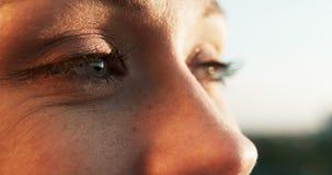 Vue de côté en gros plan des beaux yeux femelles avec le maquillage naturel La fille sourit et clignote longueur 4k banque de vidéos