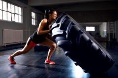 Vue de côté de femme forte poussant le pneu pendant la séance d'entraînement photo stock
