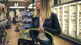 Vue de côté de femme de sourire dans le supermarché choisissant le jus dans la bouteille et mis lui dans le panier Femme de souri banque de vidéos