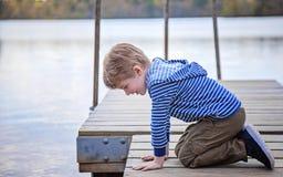 Vue de côté de garçon sur le dock regardant dans le lac Photo stock