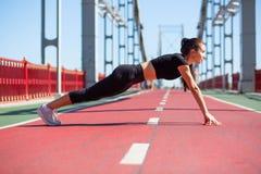 Vue de côté intégrale d'une belle femme sportive sur une position de planche images libres de droits