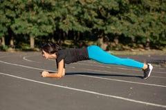 Vue de côté intégrale d'une belle femme sportive sur une position de planche image libre de droits