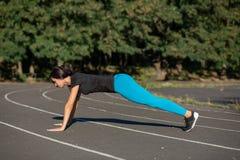 Vue de côté intégrale d'une femme assez sportive sur une position de planche images libres de droits