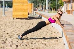 Vue de côté intégrale d'une fille adorable de forme physique faisant des pousées à la plage photographie stock