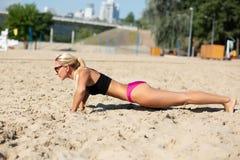Vue de côté intégrale de la fille renversante de forme physique faisant des pousées à la plage photos libres de droits
