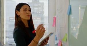 Vue de côté de jeune exécutif femelle caucasien avec le comprimé numérique travaillant au panneau en verre 4k clips vidéos