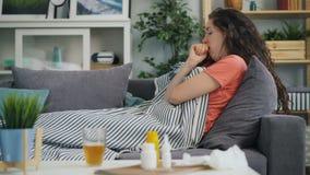 Vue de côté de jeune femme prenant la température avec le thermomètre dans la maison sur le sofa clips vidéos