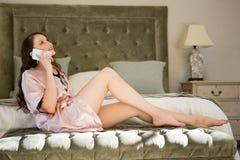 Vue de côté de jeune mariée parlant au téléphone intelligent tout en se reposant sur le lit Photo stock