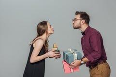 Vue de côté de jeunes couples heureux tenant des boîte-cadeau et capable embrasser Photo libre de droits