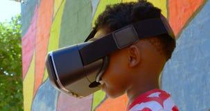 Vue de côté de l'écolier d'Afro-américain à l'aide du casque de réalité virtuelle dans le terrain de jeu 4k d'école banque de vidéos