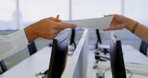Vue de côté de l'exécutif masculin donnant des documents à son collègue dans le bureau moderne 4k banque de vidéos