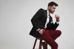 Vue de côté de l'homme assis de mode tenant des poches image libre de droits