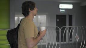 Vue de côté de l'homme avec le sac à dos marchant avec du café banque de vidéos