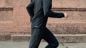 Vue de côté de l'homme commençant à courir Mouvement lent Coureur masculin établissant dans les vêtements de sport noirs Cheminem clips vidéos