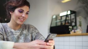 Vue de côté de la belle jeune femelle à l'aide de son téléphone portable en café et sourire Femme employant l'APP sur le smartpho clips vidéos