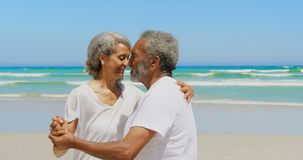 Vue de côté de la danse supérieure active romantique de couples d'Afro-américain ensemble sur la plage 4k banque de vidéos
