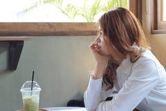 Vue de côté de la jeune femme asiatique attirante d'affaires attendant quelque chose dans le café Image libre de droits
