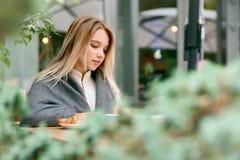 Vue de côté de la jeune séance blonde de livre de lecture de fille couverte de couverture photos stock