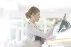 Vue de côté de la jeune serveuse sûre à l'aide de l'ordinateur tout en se tenant au compteur dans le restaurant images libres de droits