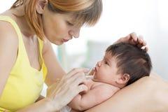 Vue de côté de la mère de soin et de son bébé infantile regardant l'un l'autre, passant le temps ensemble à la maison Images libres de droits