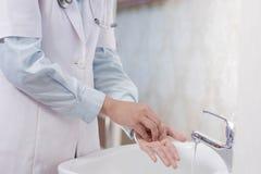 Vue de côté de la main femelle de docteur lavant sa paume dans l'évier blanc avec couler l'eau utilisant le savon et la mousse images stock