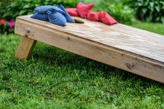 vue de côté de niveau du sol de panneau de jeu de cornhole avec des sacs sur le principal i Images stock
