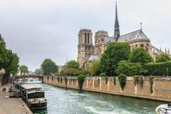 Vue de côté de Notre Dame Cathedral sur la Seine avec des péniches photographie stock libre de droits
