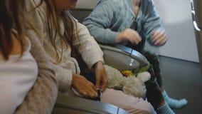Vue de côté de petites ceintures de sécurité de attachement mignonnes heureuses de garçon et de fille pendant le vol d'avion alla clips vidéos