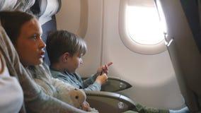 Vue de côté de peu garçon et fille ennuyés s'amusant pendant le vol d'avion allant aux vacances avec la famille clips vidéos