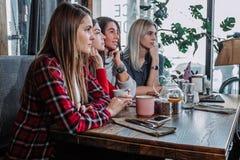 Vue de côté de quatre amis de sourire s'asseyant par la table en café Photo libre de droits