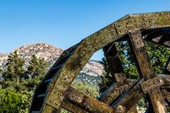 Vue de côté de roue en bois et en métal d'eau avec des montagnes photo libre de droits