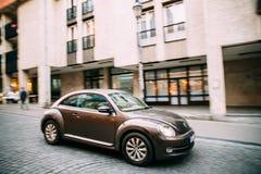 Vue de côté de voiture de coupé de berline avec hayon arrière de Brown Volkswagen New Beetle dedans Photographie stock libre de droits