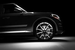 Vue de côté de voiture noire moderne de SUV dans un projecteur Images stock