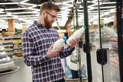 Vue de côté d'homme barbu choisissant le lait photographie stock