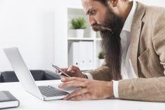 Vue de côté d'homme d'affaires avec la longue barbe regardant son pho de cellules image libre de droits