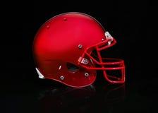 Vue de côté d'un casque de football rouge sur un fond noir Photos libres de droits
