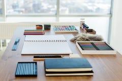 Vue de côté d'un espace de travail de peintre Le bureau en bois avec les outils artistiques s'est préparé au dessin en pastel Photos libres de droits