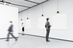 Vue de côté d'un homme avec du café regardant des affiches dans une écorchure d'art Photos stock