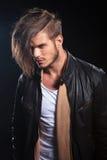 Vue de côté d'un jeune homme de mode dans des vêtements en cuir photo libre de droits