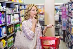 Vue de côté d'une femme assez blonde ayant un panier et regardant l'étagère Image libre de droits